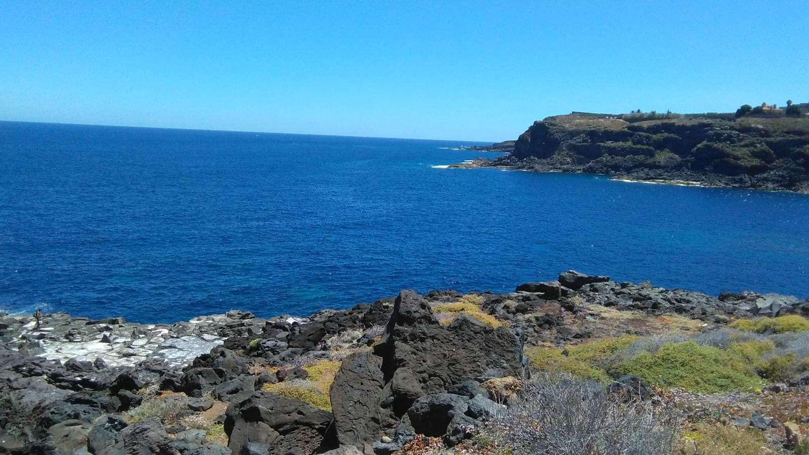 La couleur blanche des salines se détache sur la lave et le bleu de la mer